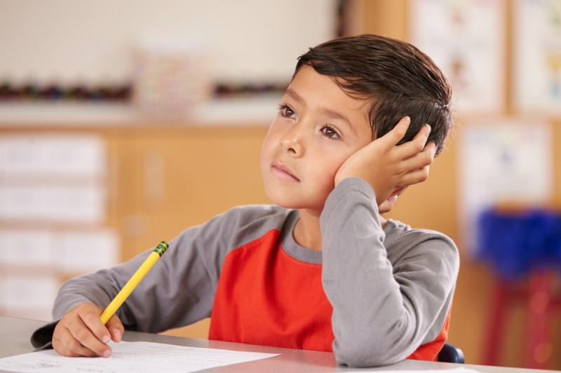Young Boy Sitting Sadly In Classroom And Thinking About Something While Listening.