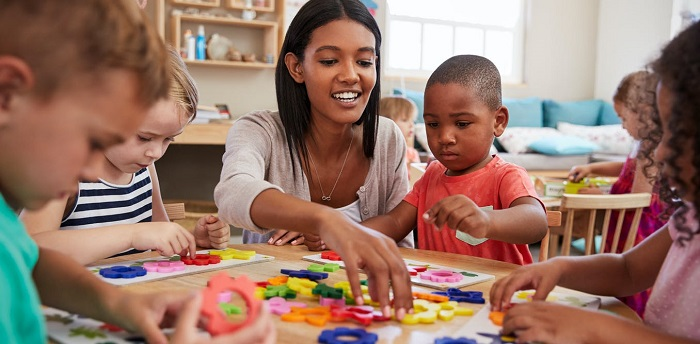 An image of a teacher helping small kids to learn using an educational kit