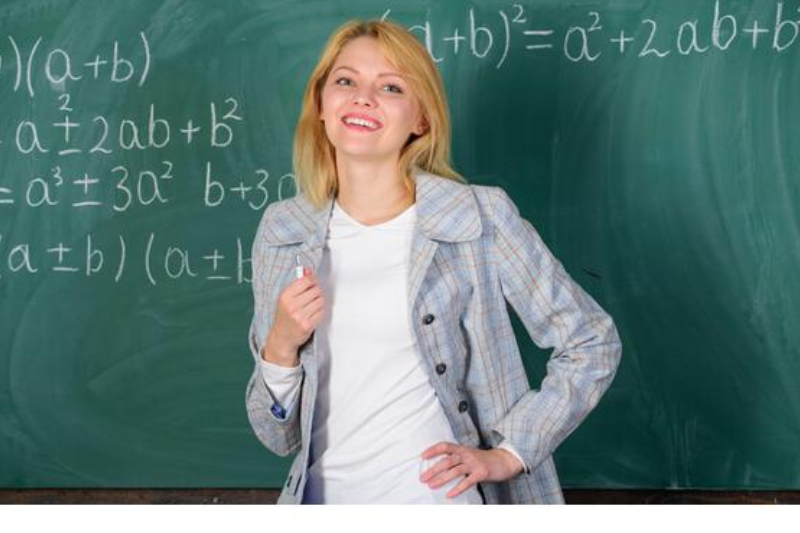 An image of a teacher with a blackboard at the background